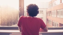 Man_looking_out_window