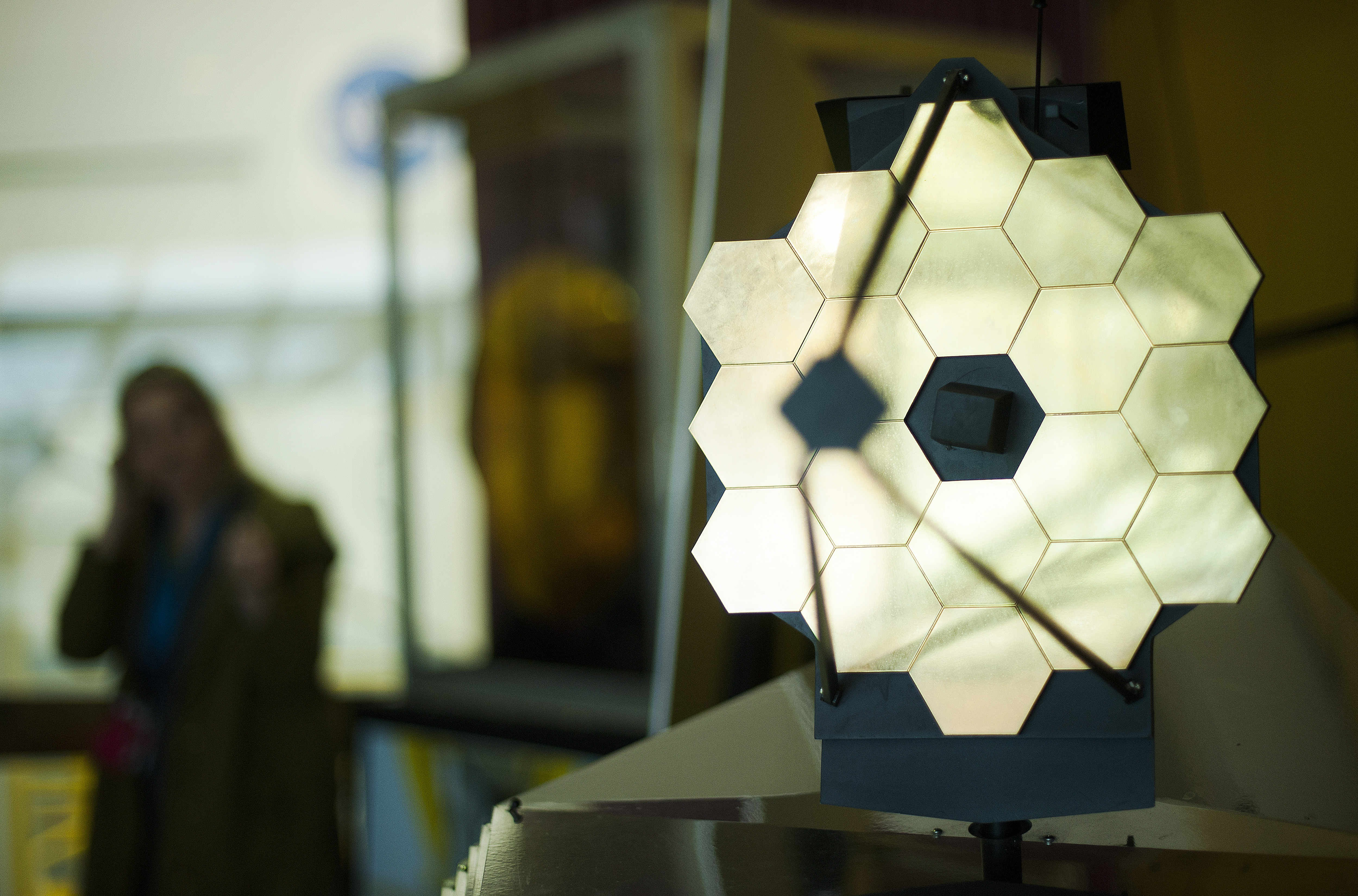 A woman stands near a model of the James Webb Space Telescope (JWST) at NASA Goddard Space Flight Center in Greenbelt, Maryland on April 2, 2015. AFP PHOTO/ JIM WATSON (Photo credit should read JIM WATSON/AFP/Getty Images)