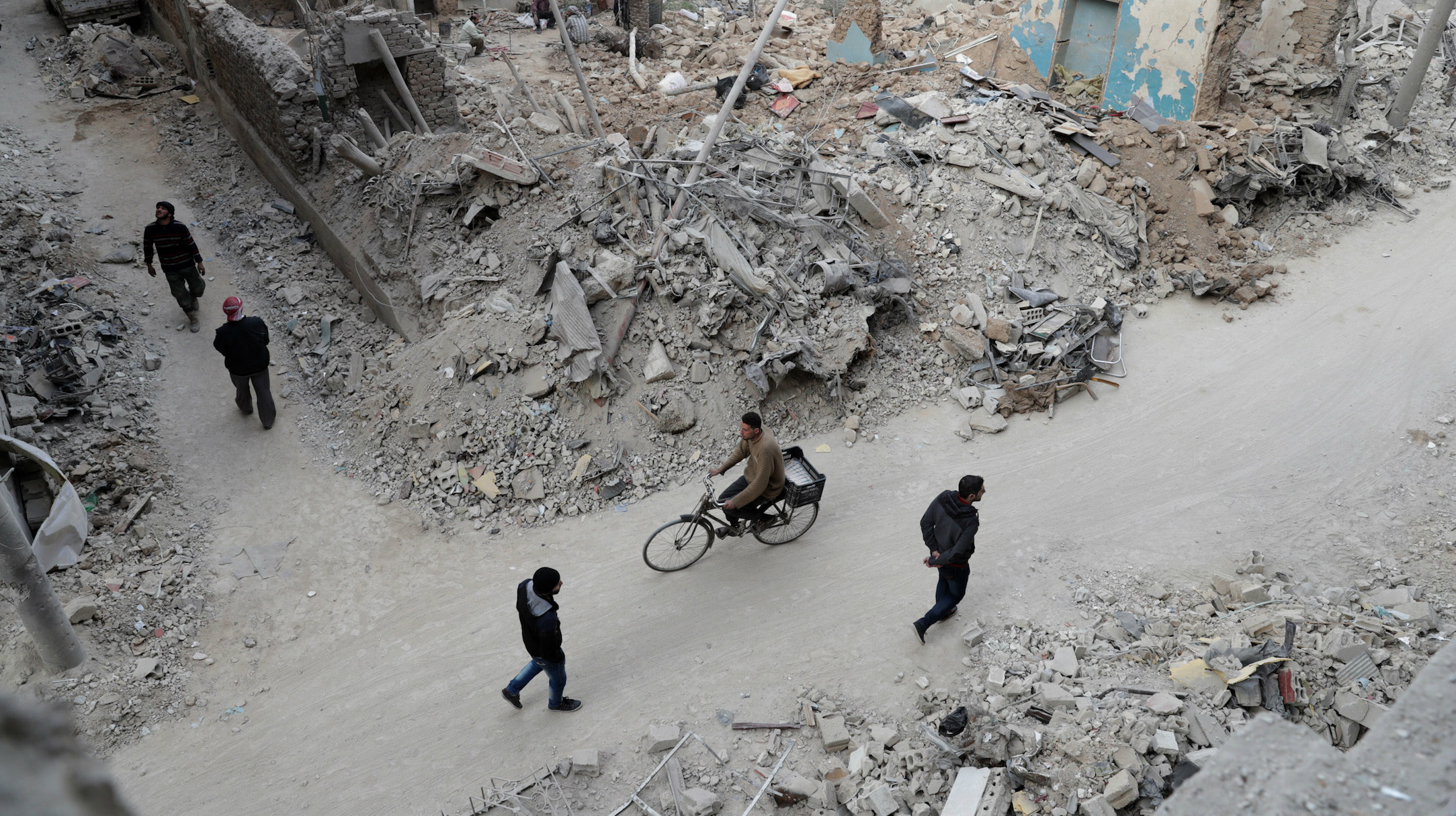 TOPSHOT - Syrians walk past the rubble of destroyed buildings in the rebel-held town of Douma, on the eastern outskirts of the capital Damascus, on February 27, 2017. Douma has witnessed government raids forcontinue despite the United Nations confirmation a few days earlier that Moscow formally asked its ally Damascus to stop launching strikes during the Geneva negotiations, which began earlier in the week. / AFP / Abd Doumany (Photo credit should read ABD DOUMANY/AFP/Getty Images)