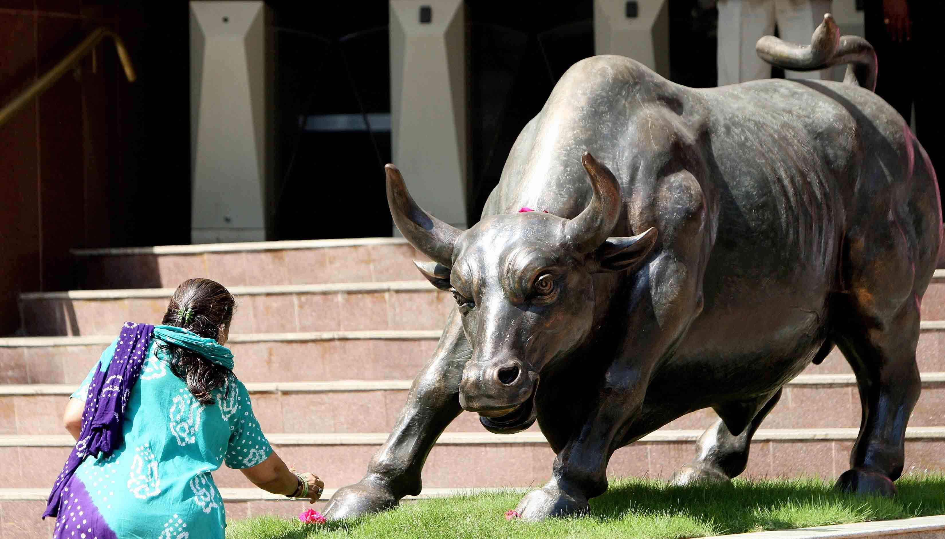 Indian woman making an offering at a statue of a bull in front of the stock market